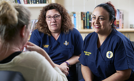 Two female mental health nurses in conversation with another woman