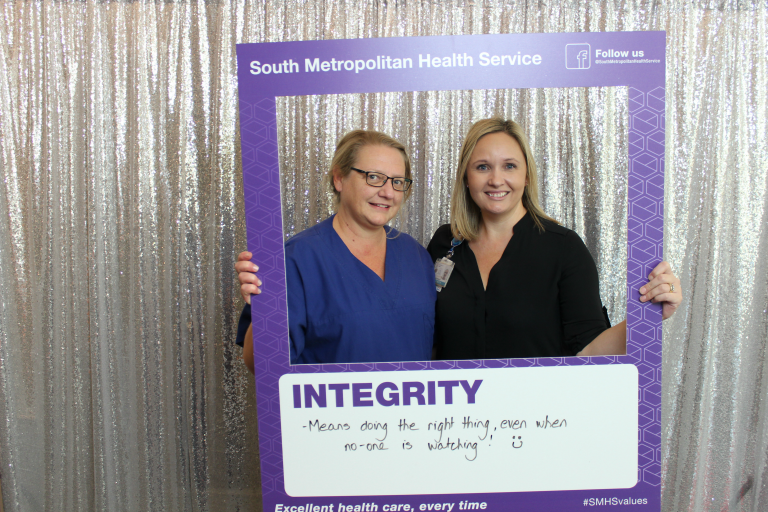 Two staff holding frame which reads Integrity means doing the right thing, even when no one is watching.