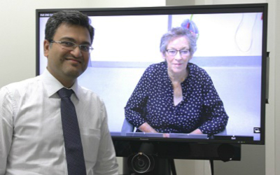 A gentleman standing in front of a television screen that features a woman on it