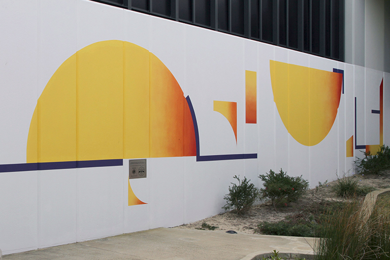 A brightly coloured wall mural in shades of yellow and orange.