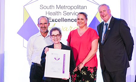 Two men and two women stand in front of a banner that reads South Metropolitan Health Service Excellence Awards. One woman holds a framed certificate.