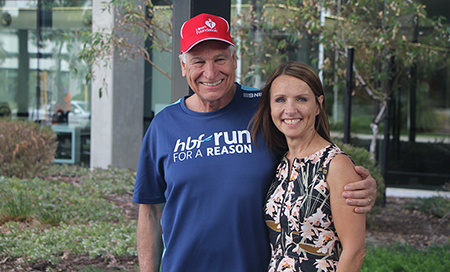 A man and a woman standing in a garden. The man wears a t-shirt reading 'HBF run for a reason'