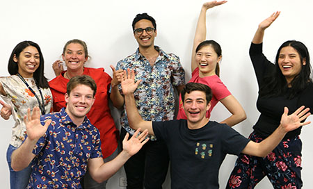 Group of staff in colourful shirts with their hands in the air