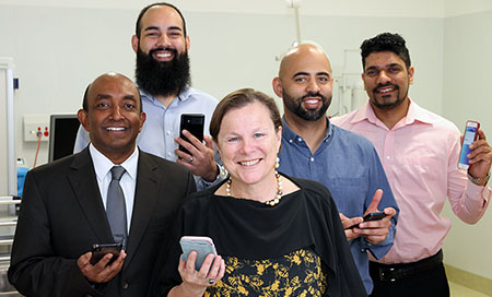 Four men and a woman standing in a treatment room. Each person is holding a mobile phone.