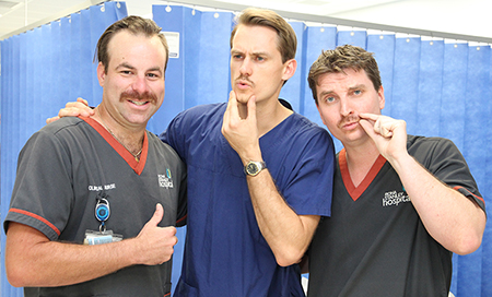 Three men standing together twiddling their moustaches