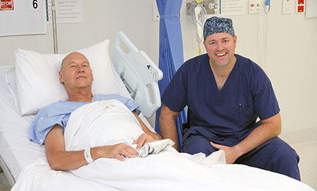 A man sits in a hospital bed. A man wearing theatre scrubs sits next to the bed.