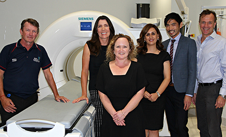Three men and three women standing beside some medical imaging equipment
