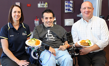 A man and woman holding plates of food sit next to a young man in a wheelchair