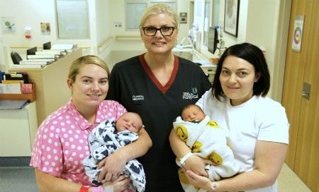A midwife with two mothers holding their babies